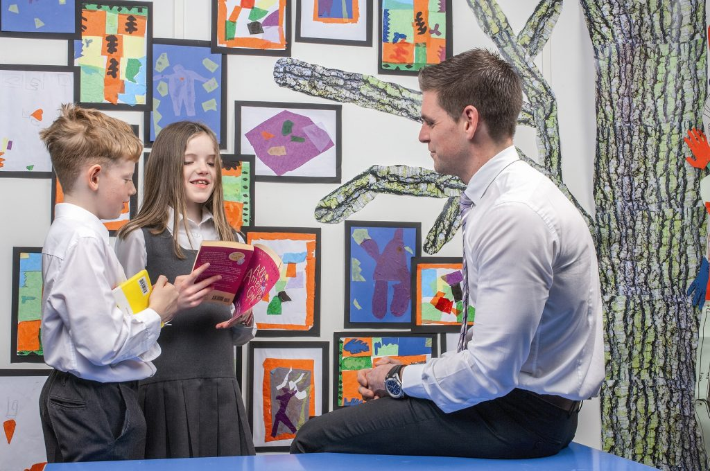 Two children with a teacher in front of a wall of paintings.