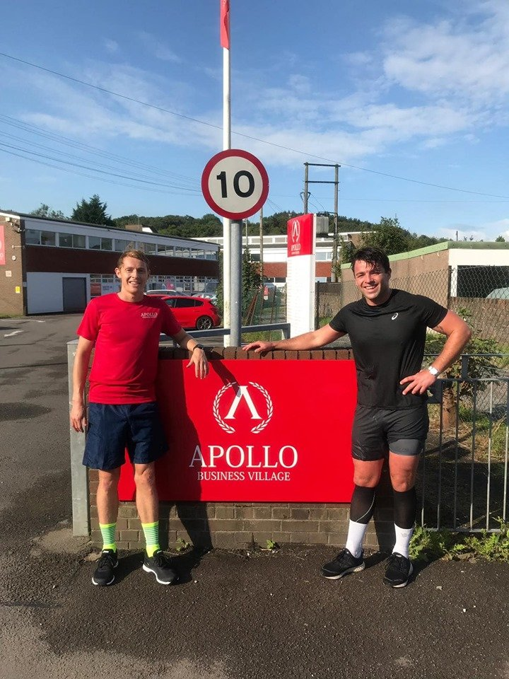 Jon and Will are standing in the sunshine in front of the Apollo Business Village office