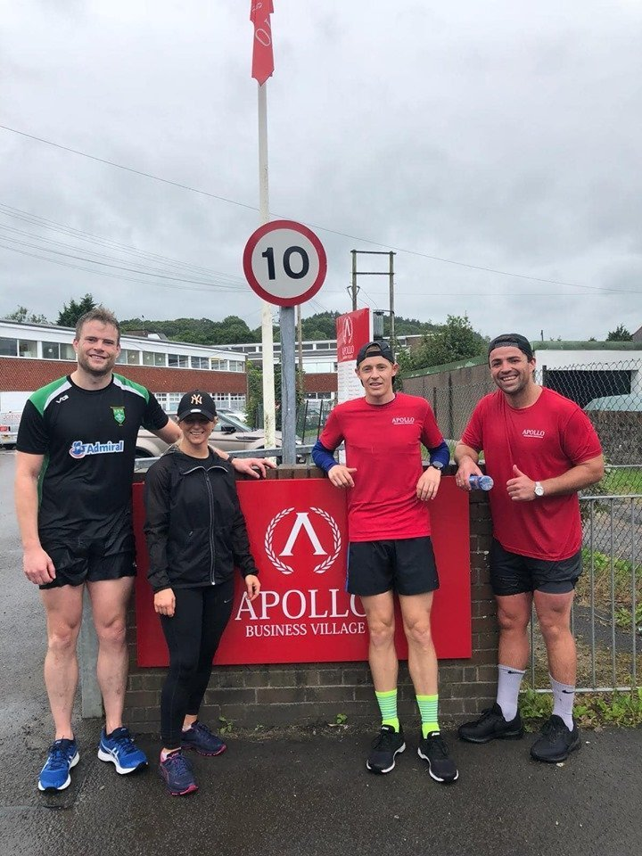 Marc, Chloe, Jon and Will standing outside the Apollo Business Village office sign