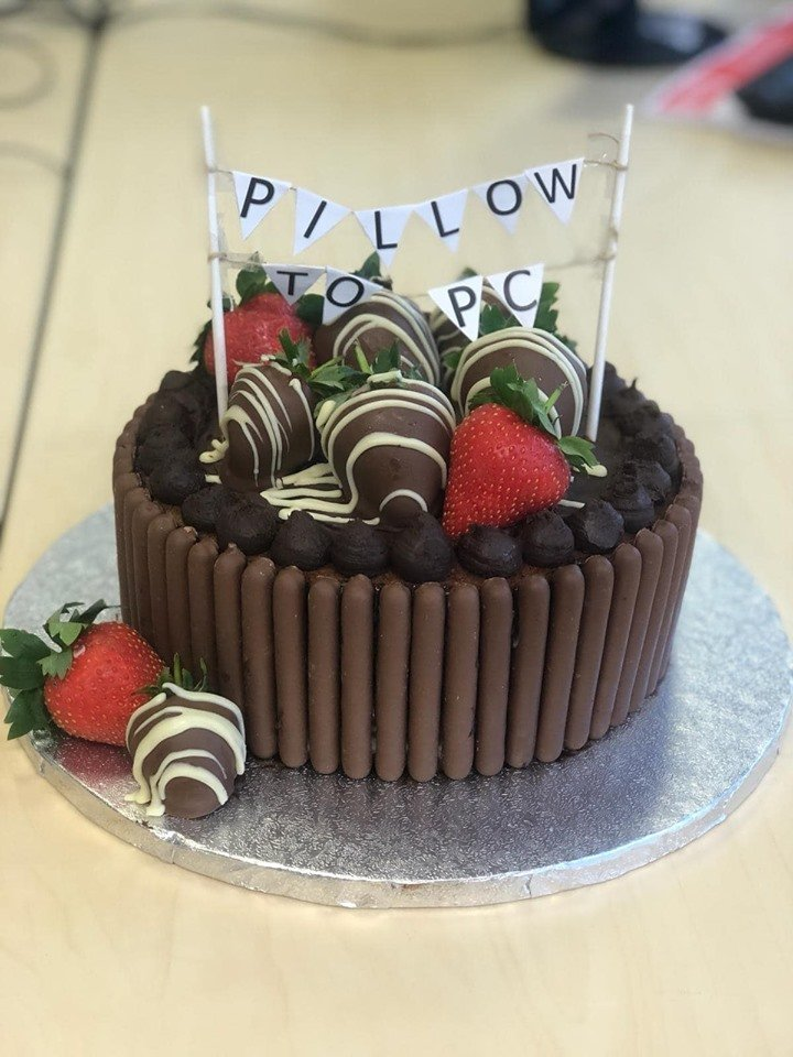 A rich chocolate cake decorated with chocolate fingers, chocolate covered strawberries and mini bunting that says 'Pillow to PC'